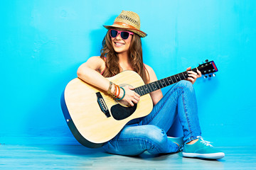 Teenager girl guitar play sitting on a floor.