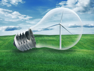 Light bulb with a wind turbine inside in green field. Environmen