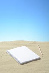 Lapicero y cuaderno en la arena