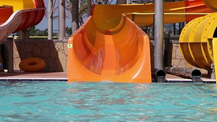 Grandpa with grandson sliding on water slide in water park