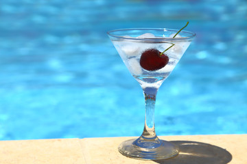 Cold cocktail with ice cubes and cherry by poolside