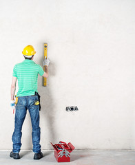 construction worker using level and other tools