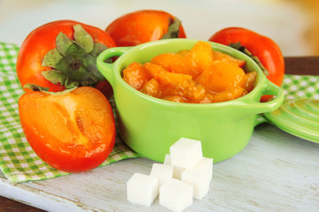 Ripe persimmons with jam in pot and sugar