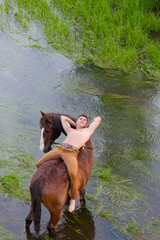 man lies on grain of the horse standing in water, and looks up