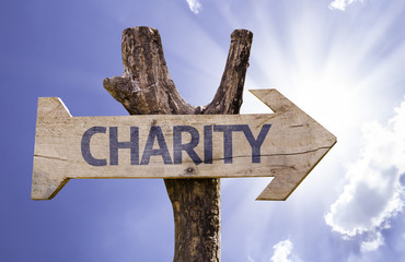 Charity wooden sign on a sky background