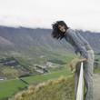 Hispanic woman leaning on fence