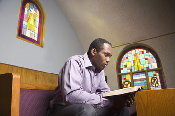 African American man reading Bible in church