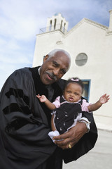 African American Reverend holding baby