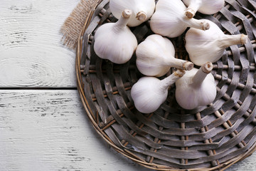 Fresh garlic on wicker mat, on wooden background
