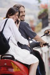Hispanic couple on scooter