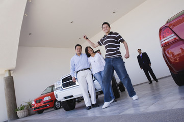 Young Hispanic man holding key for new car