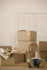 Man laying on floor next to moving boxes