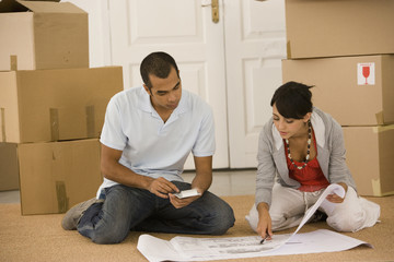 Young couple looking at blueprints in new house