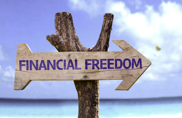Financial Freedom wooden sign with a beach on background