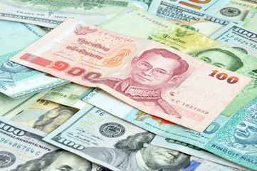 Money in multi currencies - 100 Thai Baht bill on top