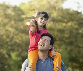 Hispanic girl sitting on father's shoulders