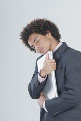 Mixed Race businessman hugging laptop