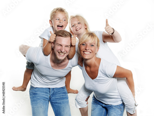 Leinwanddruck Bild Parents giving piggyback ride to children