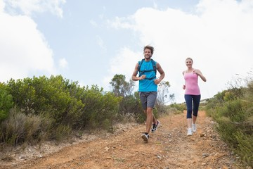 Fit attractive couple jogging down mountain trail
