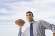 Hispanic businessman throwing football
