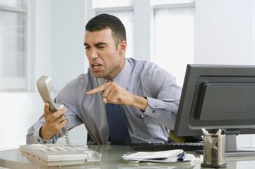 Hispanic businessman yelling at telephone