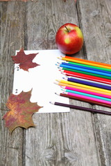 Checkered sheet, maple leaf and pencils on the wooden background