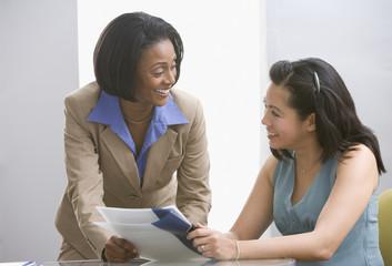 Multi-ethnic businesswomen discussing paperwork
