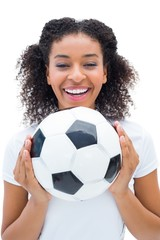 Pretty football fan in white holding ball smiling at camera