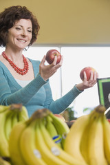Woman choosing apples at grocery store