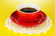 A red cup of strong coffee on yellow background