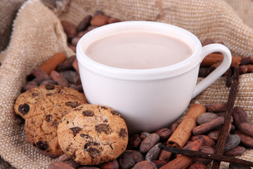 Cocoa drink and cocoa beans on sackcloth  background