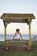 Mixed Race woman meditating near ocean