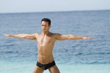 Hispanic man practicing yoga at beach