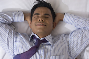 Hispanic businessman laying on bed