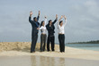 Multi-ethnic businesspeople waving at beach
