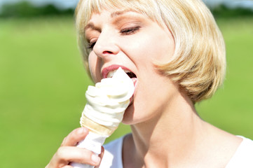 Middle aged woman eating an ice cream