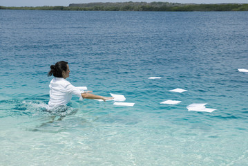 Hispanic businesswoman in water with paperwork