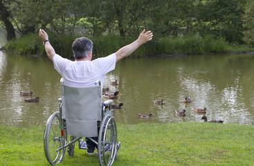 Homme en fauteuil roulant adans un parc