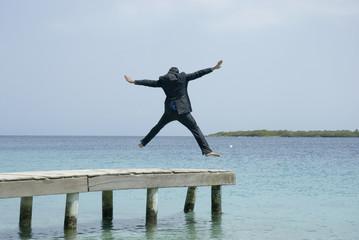 Hispanic businessman jumping on dock