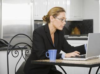 Hispanic businesswoman typing on laptop