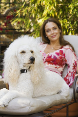 Hispanic woman on lounge chair with dog