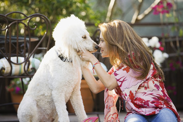 Hispanic woman rubbing noses with dog
