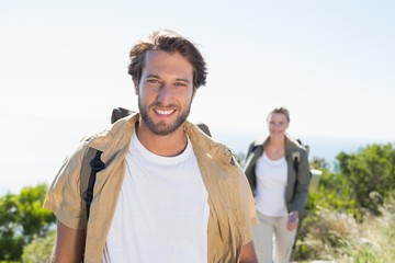 Hiking couple smiling at camera on mountain summit