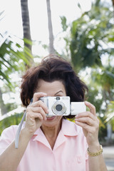 Hispanic woman taking photograph