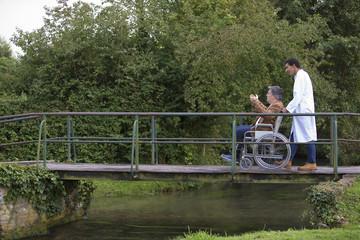 infirmier poussant un homme en fauteuil roulant dans un parc