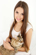 Beautiful young woman with cat sitting on bed
