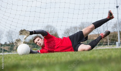 canvas print picture Goalkeeper in red saving a goal during a game