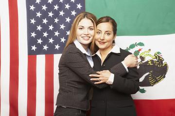 Hispanic businesswomen hugging