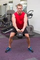 Strong man lifting heavy kettlebell