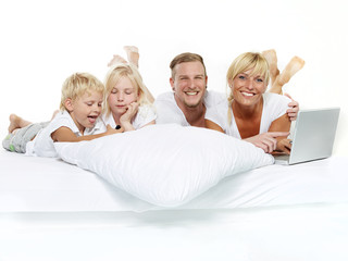 Happy family with laptop stay in bed
